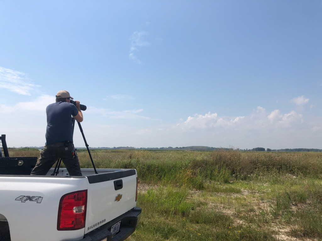 Technician standing in a truck bed, looking through a spotting scope to evaluate wetlands extending in from of them.